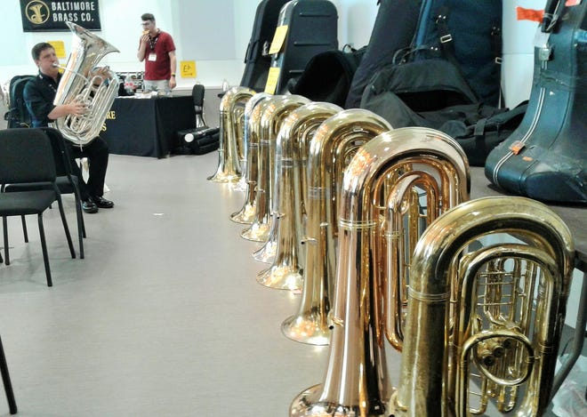 Vendors filled rooms at Voxman Music Building with their best tubas and euphoniums during last week's conference in Iowa City. In this photo, a visiting music professor tries out a Mack Brass Custom.