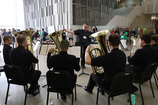 """John Manning conducts """"College Tubum,"""" the University of Iowa's tuba-euphonium ensemble, in the conference's opening evening performance in the Pearl West Lobby of the Voxman Music Building. Manning also served as conference coordinator."""