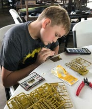 Jack Hamby of Madison carefully glues together a miniature for the Flames of War games.