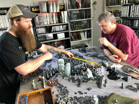 Will Cooper of Pearl, left, and Jeff Chisolm of Union prepare to play the Age of Sigmar fantasy game, using armies of miniature warriors.