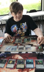 Christian Bradford of Richland checks his cards for Magic: The Gathering game.