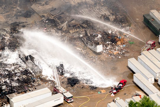 Firefighters spray a fire retardant foam onto a fire at Fort Loudon Waste & Recycling as seen in this aerial photograph taken from an airplane in Knoxville, Tennessee on Thursday, May 2, 2019.