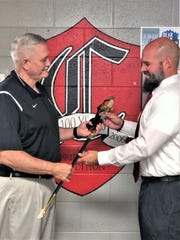 Michael Reynolds presents new Central High School principal Andrew Brown with an officer's sword, symbolically passing the torch, on May 31, 2019.