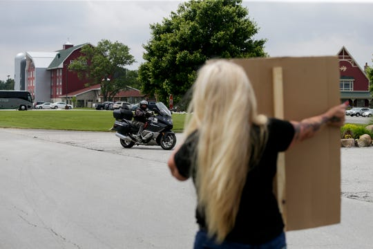 Tanya Webb of Cedar Lake holds a sign as she protests outside the entrance to Fair Oaks Farms, Wednesday, June 5, 2019, in Fair Oaks.