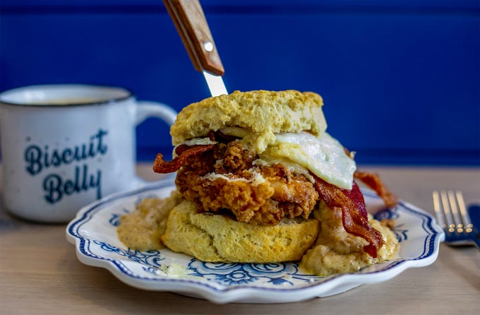 The Rockwell Supreme buiscuit at Biscuit Belly is served with fried chicken, cheddar cheese, goetta sausage gravy, bacon and an over easy egg. June 5, 2019