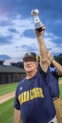 Grand Ledge coach Pat O'Keefe raises the Diamond Classic championship trophy at McLane Stadium, MSU, East Lansing, Michigan, Tuesday, June 4, 2019.