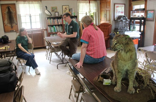 Nathan Roberts (center), a wildlife researcher with the Wisconsin Department of Natural Resources, speaks about bobcats during a presentation at Hawthorn Glen Outdoor Recreation Center in Milwaukee. The life-size bobcat mount in the right foreground was donated by a Wisconsin hunter for permanent display at the center.
