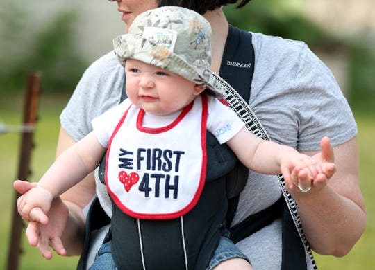 Lucas Menke,  6 months, enjoyed his first Fourth of July parade in Wauwatosa from the safety of his mother Kristy Menke's arms.