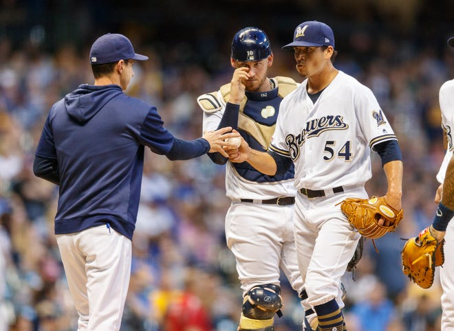 Brewers pitcher Taylor Williams hands the ball to manager Craig Counsell during a game last season.