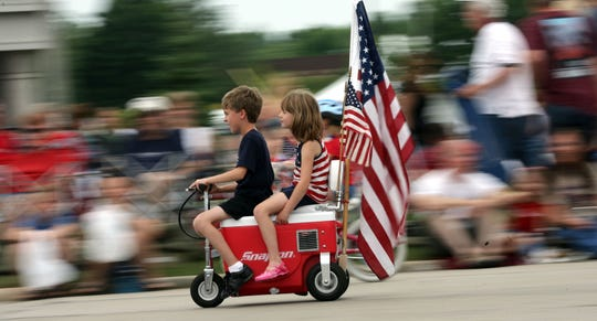 Youngsters ride a scooter in the City of Franklin Fourth of July Parade on Loomis Road Saturday, July 4, 2009, in Franklin.