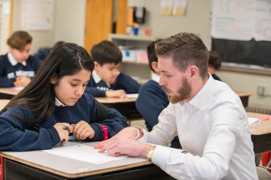 Nikolas Hansen, a middle school math teacher at LUMIN schools, teaches student Joselin.