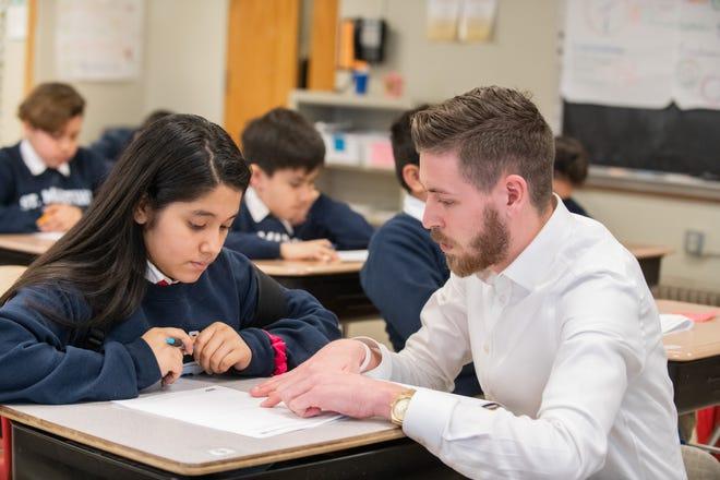 Nikolas Hansen, a middle school math teacher at LUMIN schools, teaches student Joselin.