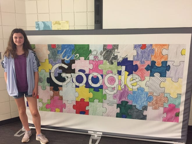 """Ella Hannes, a seventh grade student at Kettle Moraine Middle School, stands next to her Doodle for Google submission called """"We All Fit."""""""