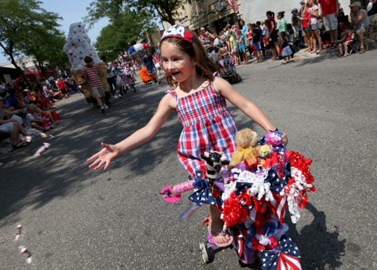 Madison Gosa, 5, of Pewaukee tosses candy to spectators along the parade route from her decorated bike, as she rides in the Fourth of July parade in downtown Waukesha in 2012.