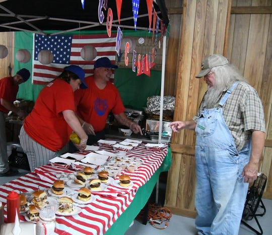 Members of the Holy Smokes BBQ team talk with a Taste of the Twin Lakes attendee Tuesday night. The Mountain Home barbecue restaurant won the evening's People's Choice Award.