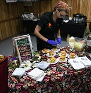 A member of the Cooyon's Restaurant team prepares shrimp sliders Tuesday night at the Taste of the Twin Lakes fundraiser. Cooyon's fish and shrimp coubion and shrimp sliders was judged to be the night's best entree by a panel of judges.