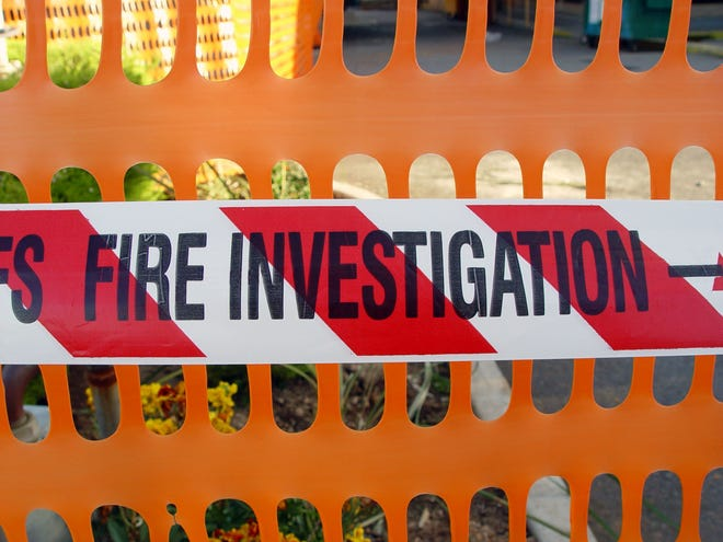 """""""White, red and black fire investigation tape, in front of an orange plastic fence to keep the public back."""""""