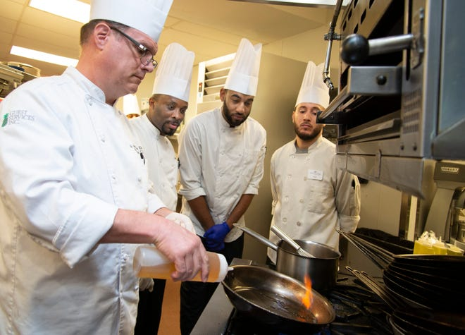 Moorings Park's Chef Wilbur (Billie) Raper, Jr., demonstrates cooking techniques as several apprentices from the American Culinary Federation Education Foundation look on.