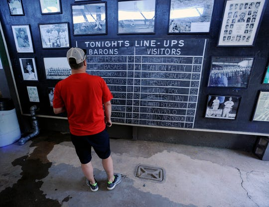 Brian Schwarberg studies the chalk lineup board before a Double-A baseball game between the Birmingham Barons and the Montgomery Biscuits at Rickwood Field, America's oldest baseball park, in Birmingham, Ala., Wednesday, May 29, 2019. Built in 1910, the ballpark predates better-known parks including Chicago's Wrigley Field and Fenway Park in Boston. Schwarberg said he drove nine hours from his home in Illinois to see Rickwood.