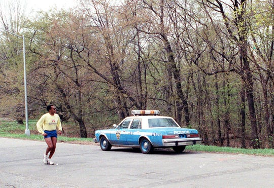 In this April 21, 1989 file photo, a jogger passes a New York City police vehicle parked near the area where a woman, who came to be known as the Central Park jogger, was raped, beaten and left for dead two nights earlier.