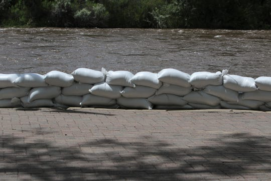 Sandbags line the banks of the Animas River, Wednesday, June 5, 2019, at All Veterans Memorial Plaza in Berg Park in Farmington. The plaza was declared temporarily off-limits by the city on  June 7 due to rising river levels.