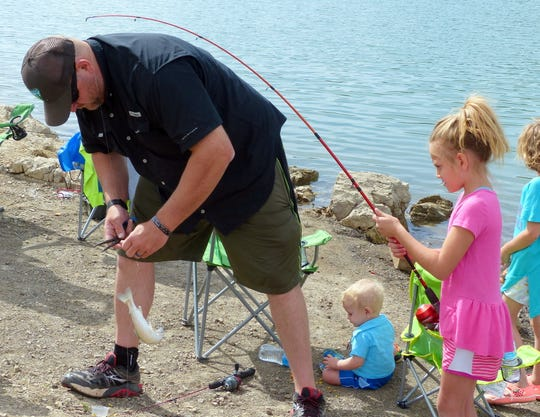 A father helps his daughter unhook her first fish during an annual youth fishing day at Grindstone Reservoir. The event is Satyurday, June 15 this year.
