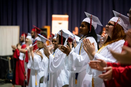 Seniors clap along to Port Huron High School's fight song at the conclusion of the school's 151st commencement ceremony Tuesday, June 4, 2019 at McMorran Arena.