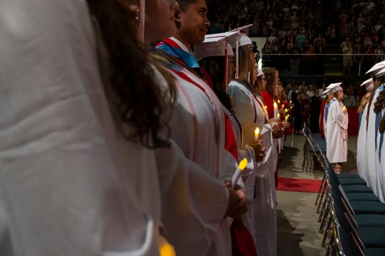 Graduating seniors participate in the processional of lights at the start of Port Huron High School's  151st commencement ceremony Tuesday, June 4, 2019 at McMorran Arena.
