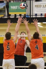 Central York's Braden Richard, center, leaps to hit the ball over the outstretched arms of Northeastern's Nate Wilson (5) and Zech Sanderson (4) in a PIAA Class 3A boys' volleyball state semifinal Tuesday, June 4, 2019 at Red Lion.
