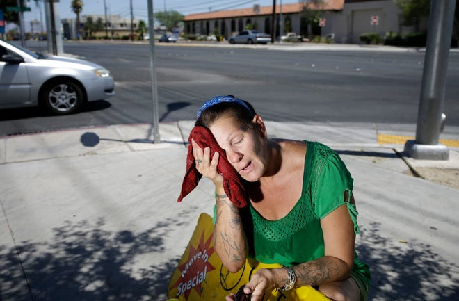 Temperatures in the mid- to upper 90s as far north as Wisconsin are expected to hit part of the country over the weekend and into next week.    John Locher/AP Amanda Ouellet wipes her face with a cold wet towel to cool off while working outside holding an advertising sign Tuesday, July 1, 2014, in Las Vegas. Temperatures will soar above 95 degrees for much of the central U.S. this weekend.