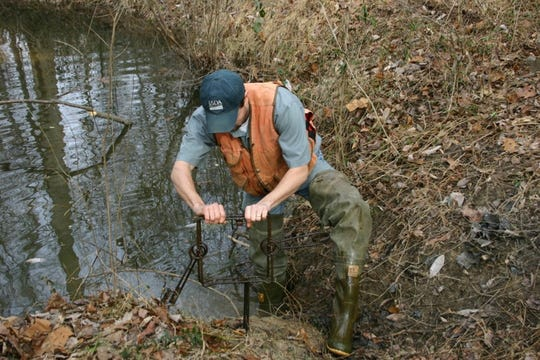 A USDA employee prepares a body hold trap for beavers.