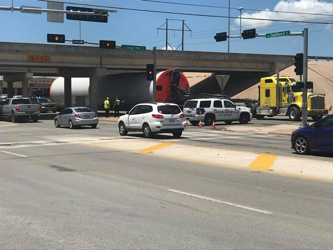 A truck carrying an oversize load gets stuck under the Loop 306 in the 3900 block of the Loop 306 Frontage Road Wednesday, June 5, 2019.
