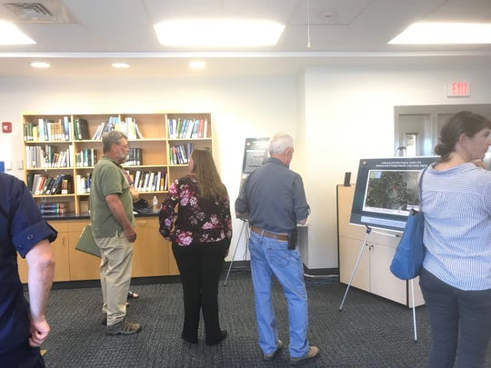 Members of the public look at displays during an informational meeting about an Army Corps proposal for beneficial use of dredge spoils in Wachapreague, Virginia on Tuesday, June 4,  2019.