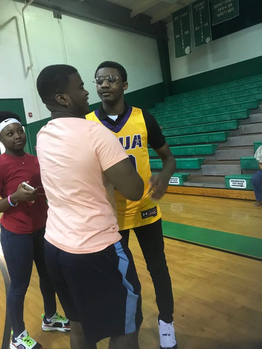 Kaalas Roots visits with a friend before signing with LSUA Tuesday night at the school.