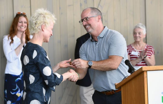 """Jennifer Kirby receives a City of Sioux Falls """"challenge coin,"""" used to support the core values of Sioux Falls, as recognition for her work as the board chair for the Levitt at the Falls outdoor music venue at the ribbon cutting ceremony Wednesday, June 5, in Sioux Falls."""