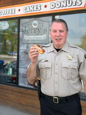 Pennington County Sheriff Kevin Thom holds his favorite bacon doughnut outside Jerry's Cakes & Donuts in Rapid City.