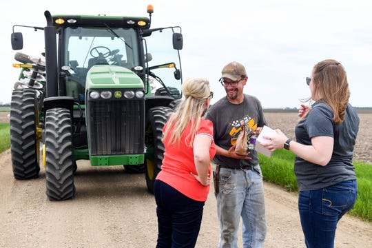 Courtney Drenth and René Stolsmark from the Chamber of Commerce find Eric Fick working in the field Tuesday, June 4. The Chamber provided small care packages to local farmers and sent representatives to hear from them how business is expected to change for the season.