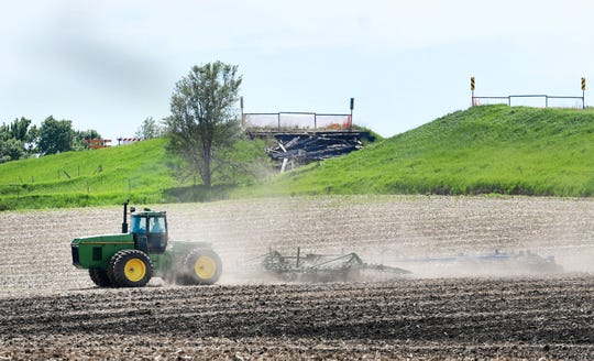 A local farmer works the land near a completely flooded-out road Tuesday, June 4.