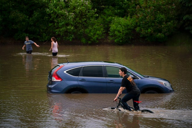 Austin Schiff pedals past a vehicle stranded in flooded water near Lakeville North High School in Lakeville after heavy rain early Tuesday evening, June 4.