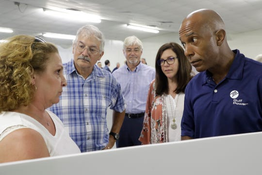 Gulf Power external affairs employee Timothy Bryant, right, and Tram Road resident Catherine Delaney, left, tensely discuss the route of Gulf Power's proposed transmission power line near Delaney's residence as others listen in during a meeting held by NextEra with the public about the proposed project at the North Florida Fairgrounds Tuesday, June 4, 2019.