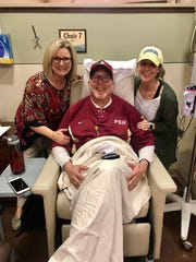 Florida State alum and former baseball umpire Nick DiLuzio shows is upbeat spirit after a treatment at the Tallahassee Memorial Cancer Center. He's joined by his wife Lorie (left) and daughter Kaitlin (Chiles High School volleyball coach).
