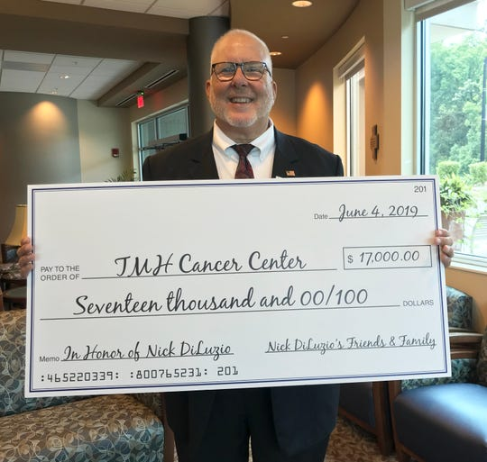 Former veteran umpire Nick DiLuzio holds a check for $17,000 donated in his honor to the TMH Cancer Center on Tuesday, June 4, 2019.