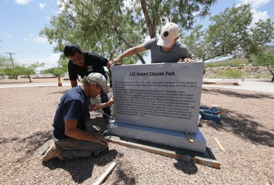 """Employees of Zamorano's Monument Co. muscle a 1,500-pound granite monument into place honoring World War II, Korean War and Vietnam War veteran Robert E. """"Bob"""" Chisolm at Chisolm Park in northeast El Paso. A D-Day celebration hosted by the Benavidez Patterson All Airborne Chapter 82nd Airborne Division Association."""