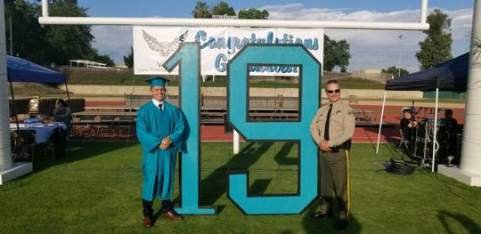 Juan Bravo and Tulare County Sheriff Mike Boudreaux take a photo on Bravo's graduation from Visalia Charter Independent Study.