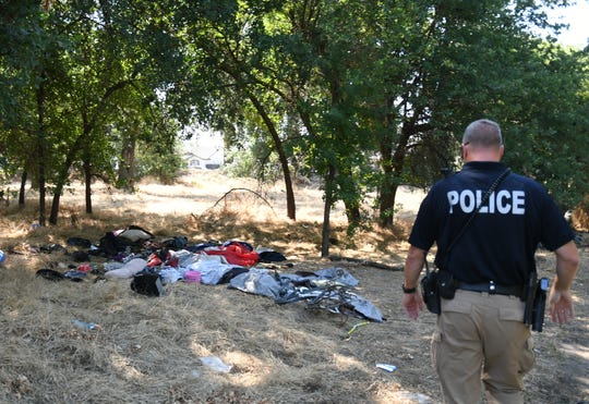Sgt. Brent Miller of the Visalia HOPE Team oversees a clean up of many abandoned homeless camps on private land along Mill Creek Trail.