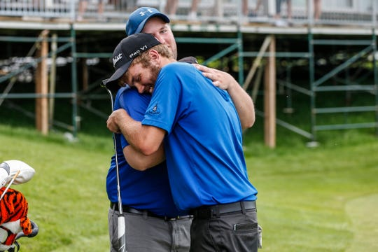 Merrill's Russell Dettmering embraces coach Andy Plisch after winning the Division 1 state golf championship Tuesday in Madison.
