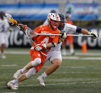 Mamaroneck's Thomas Conley winds up for  a shot on goal as he's covered by Massapequa's Jake Mcnally during the  Class A State Semi Final in Albany on June 5, 2019.