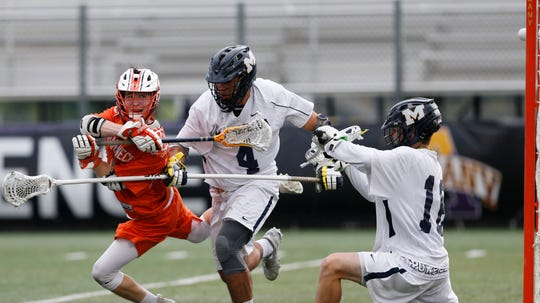 Mamaroneck's Thomas Conley takes a shot on goal through Massapequa's, from left, Dan Callan and Nicholas Squicciarini during the Class A State Semi Final in Albany on June 5, 2019.