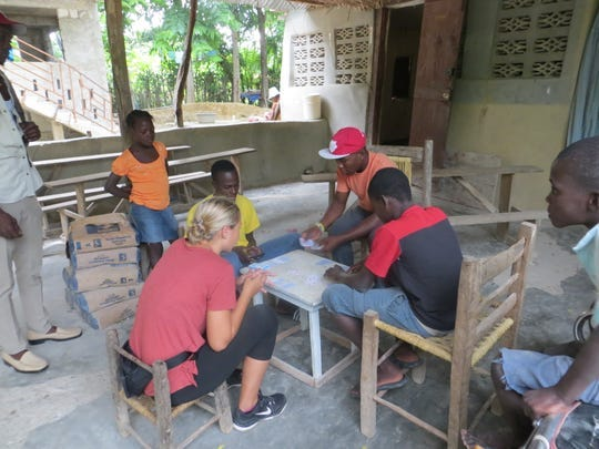 Katrina Pokorny plays a card game with residents during her mission trip to Haiti in 2017.