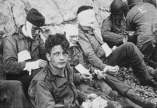 US soldiers of the 16th Infantry Regiment, wounded while storming Omaha Beach, waiting by the chalk cliffs for evacuation to a field hospital for treatment.
